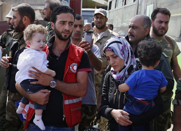 Image: Staffers of the Syrian Arab Red Crescent assist families of gunmen as they leave from Al-Waer