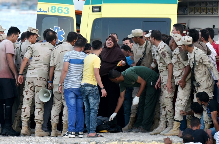 Image: Egyptian policemen and medics stand over a body of a migrant along the shore in the Egyptian port city of Rosetta