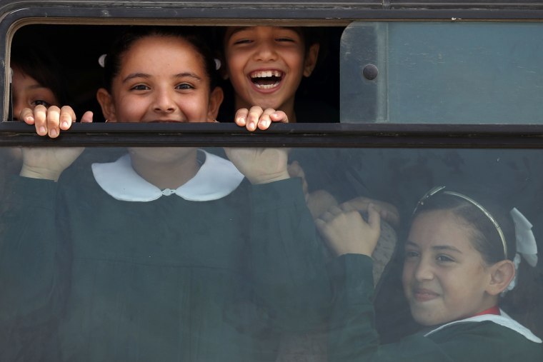 Image: Palestinian school girls smile to the camera as they come back home in their school bus