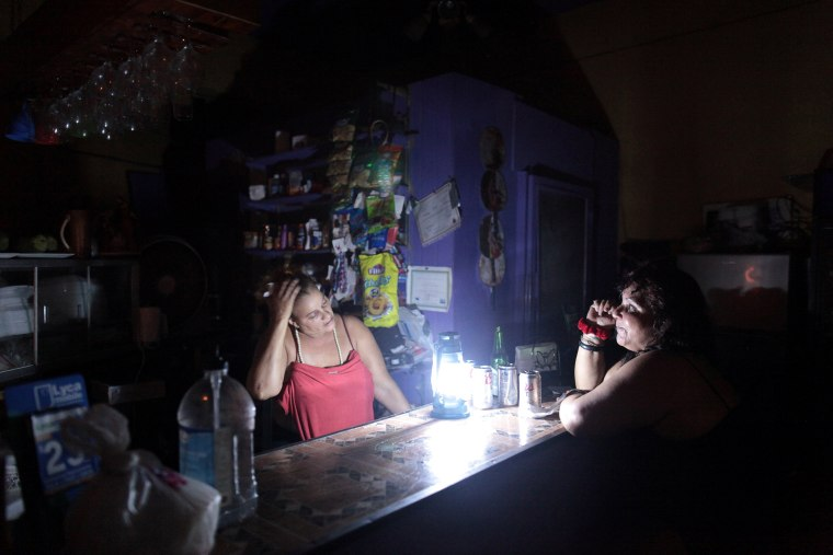 Image: Flor Dalisa Contreras talks with Virginia Rivas at a coffee shop during a power outage that affected several areas in the country, in San Juan