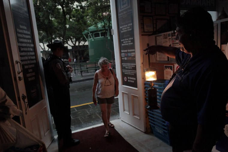 Image: A client enters a drugstore during a power outage after a fire at an energy plant knocked out electricity for the bulk of the island, in San Juan