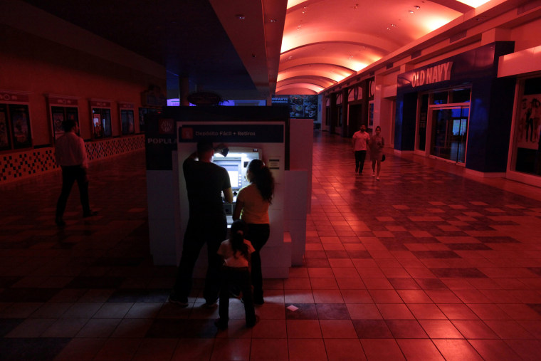 Image: People use an ATM machine at a shopping mall during a power outage that affected several areas in the country, in San Juan