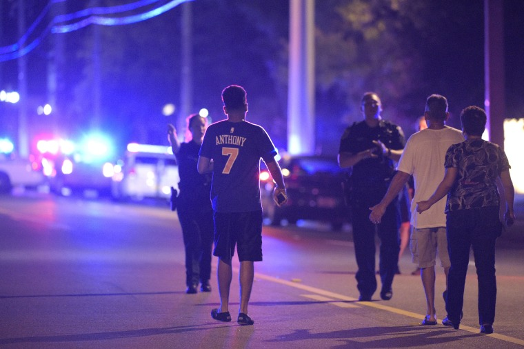 In this photo taken June 12, 2016, Orlando Police officers direct family members away from a shooting involving multiple fatalities at the Pulse Orlando nightclub in Orlando, Fla.