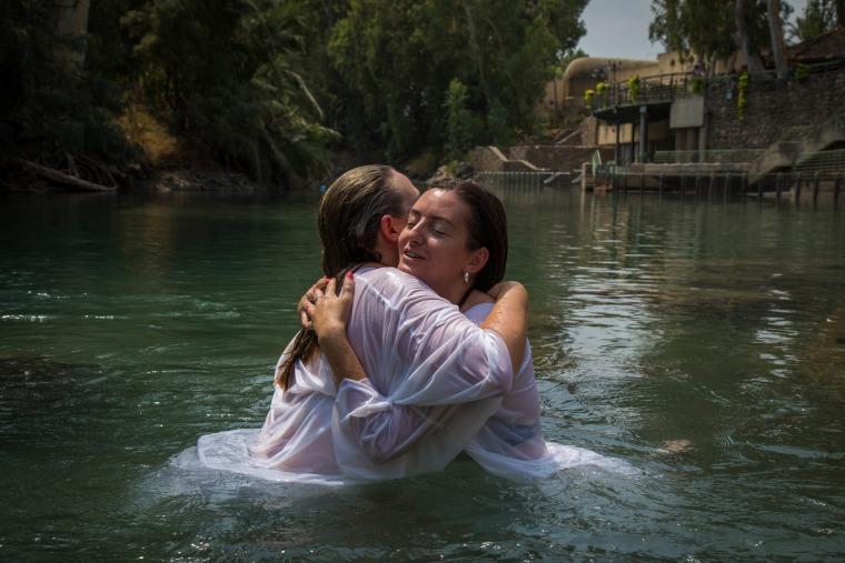 Image: U.S. veterans Katherine Ragazzino and Jackie Ann Kirkwood hug after being baptized in the Jordan River in northern Israel.