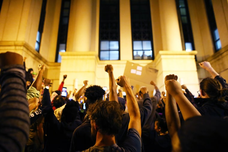 Image: Protesters hold a moment of silence at the police station for a protester that died during protests September 21 during another night of protests over the police shooting of Keith Scott in Charlotte