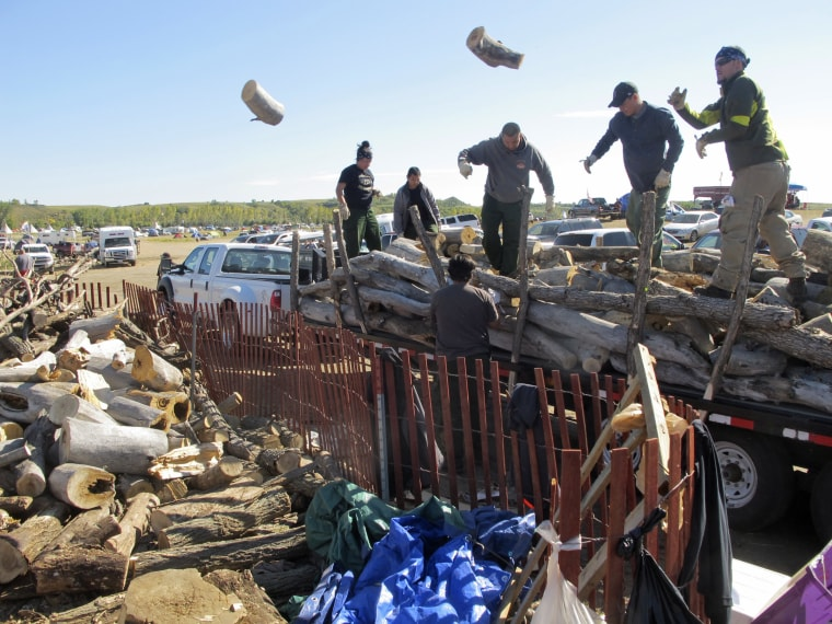 In this Wednesday, Sept. 14, 2016, photo, volunteers toss logs at an oil pipeline protest encampment near the Standing Rock Sioux Reservation in southern North Dakota. The logs will be used to cook meals for the thousands of people who have come to the area to fight the $3.8 billion Dakota Access pipeline.