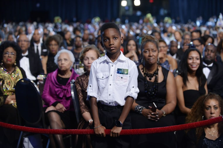 Image: A young boy listens to President Barack Obama as he speaks at the Congressional Black Caucus Foundation