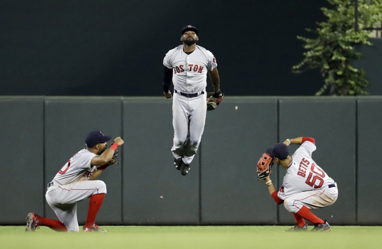 Image: Boston Red Sox outfielders celebrate after a baseball game
