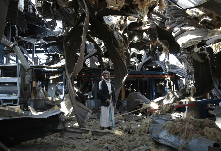 Image: An elderly man stands among the rubble of the Alsonidar Group's water pump and pipe factory after it was hit by Saudi-led airstrikes in Sanaa