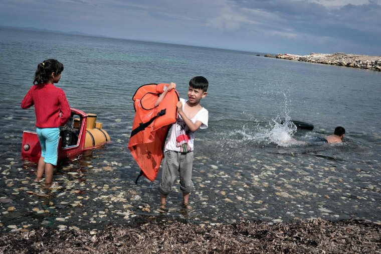 Image: Children play on the beach at an unofficial refugee site run by activists on the island of Lesbos