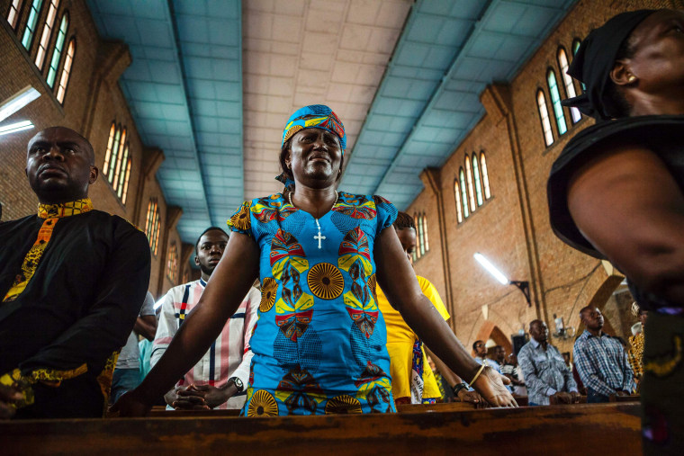 Image: A woman cries as she attends a Catholic mass in Kinshasa