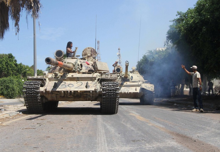 Image: Members of Libyan forces allied with the U.N.-backed ride their tanks during a battle with Islamic State militants in Sirte