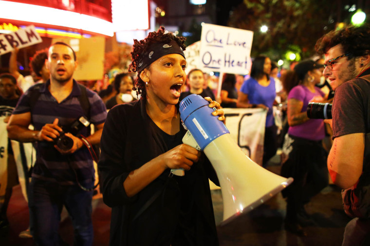 Image: A protester speaks through a megaphone during another night of protests over the police shooting of Keith Scott in Charlotte