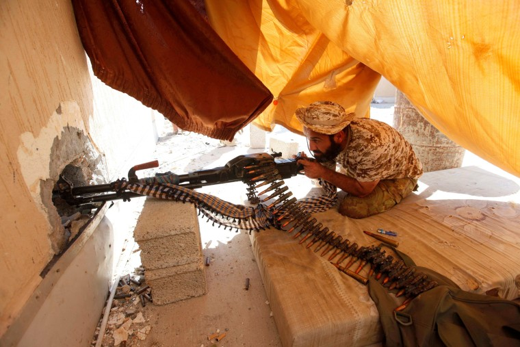 Image: Fighter from Libyan forces allied with the U.N.-backed government aims his weapon as he takes a position on a building rooftop during a battle with Islamic State militants in Sirte