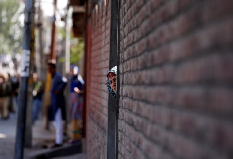 Image: A woman looks out from a door during a protest in Srinagar, against the recent killings in Kashmir region