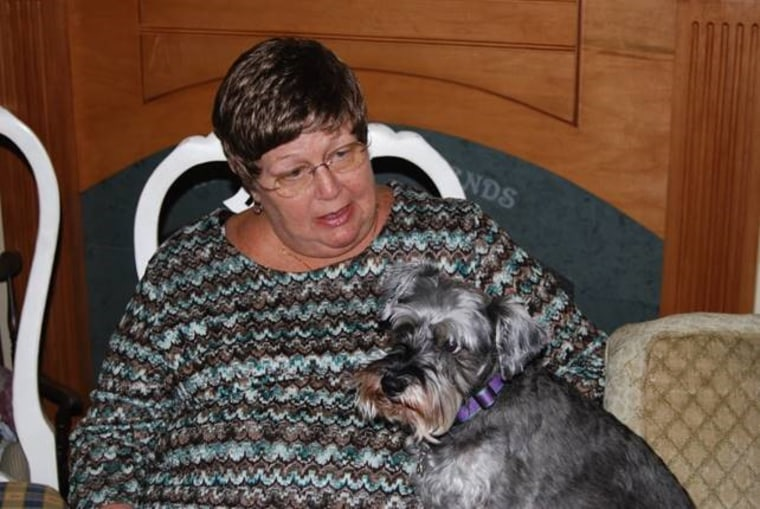Louann VanKoevering holds one of her miniature schnauzers on her lap.