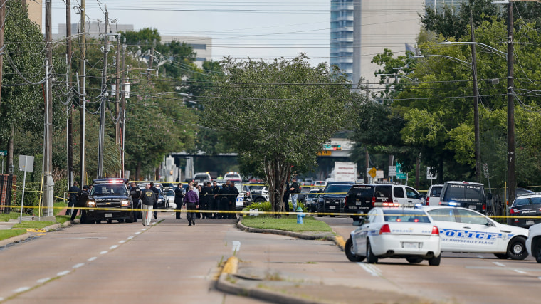 Image: Investigators look over the scene where nine individuals were shot at a strip mall