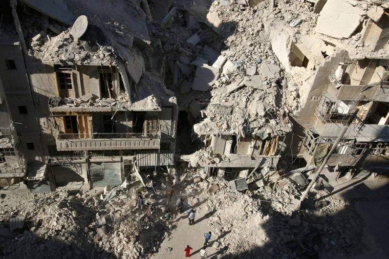 Image: People dig in the rubble in an ongoing search for survivors at a site hit previously by an airstrike in the rebel-held Tariq al-Bab neighborhood of Aleppo