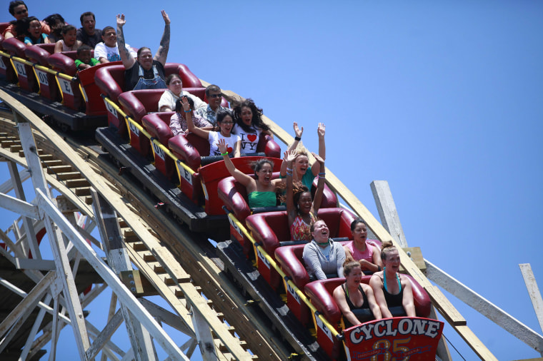 Image: People ride the Cyclone roller coaster at Coney Island in the Brooklyn borough of New York