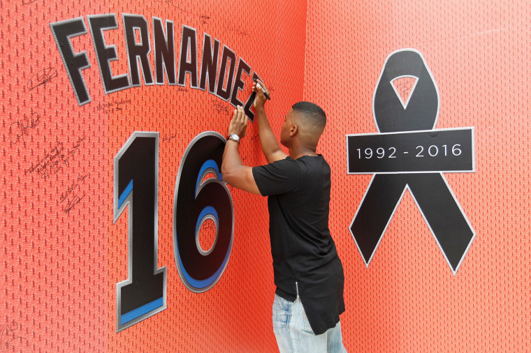 Image: A fan signs the memorial mural as he mourns the death due to a boating accident of Miami Marlins pitcher Jose Fernandez, outside Marlins Park prior to a game against the New York Mets in Miami