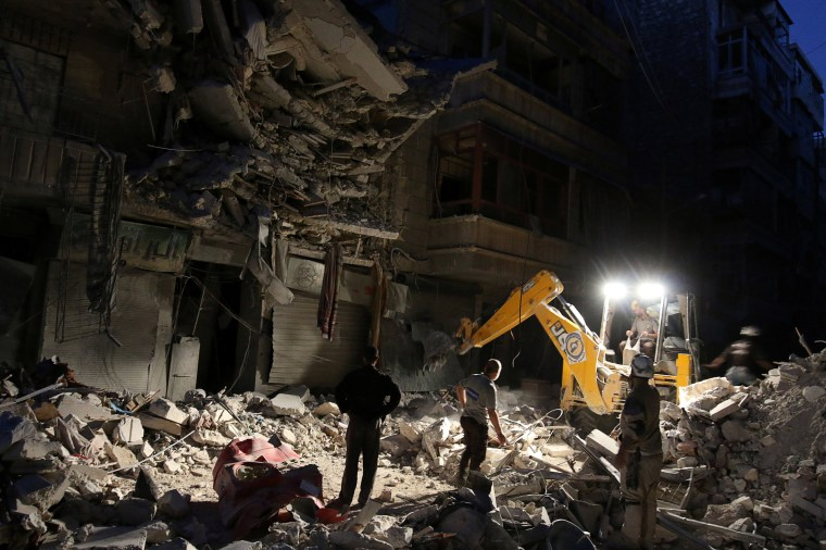 Image: Civil Defense members search for survivors at a site hit by an airstrike in the rebel-held al-Shaar neighbourhood of Aleppo