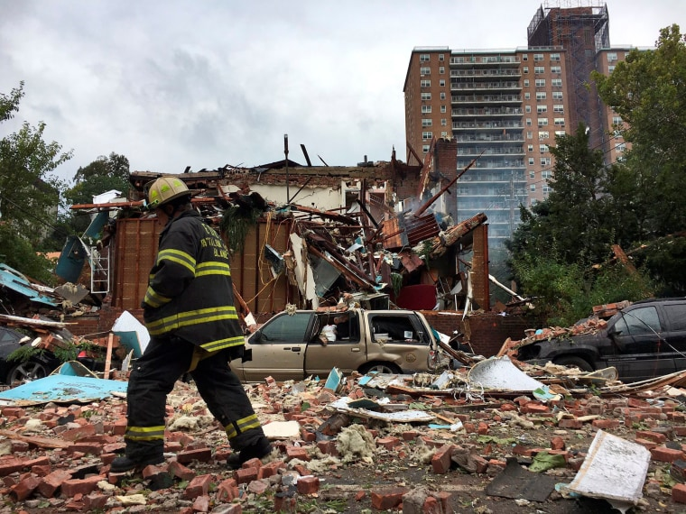 Image: A New York City firefighter walks through debris after an explosion ripped through a home in the New York City borough of the Bronx, New York