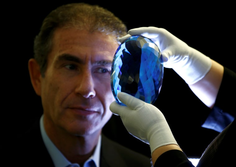 Image: Philanthropist Maurice Ostro looks through his Ostro stone, the largest known blue topaz stone, for media at the Natural History Museum in London