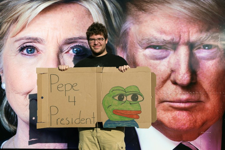 Image: Ben Wilke, 19, poses outside the first presidential debate with a sign featuring Pepe the Frog.