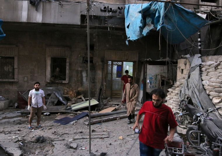Image: Medics inspect the damage outside a field hospital in Aleppo