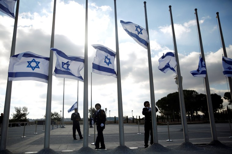 Image: Israeli presidential guards lower the national flag to half mast during a ceremony marking the death of former Israeli President Shimon Peres