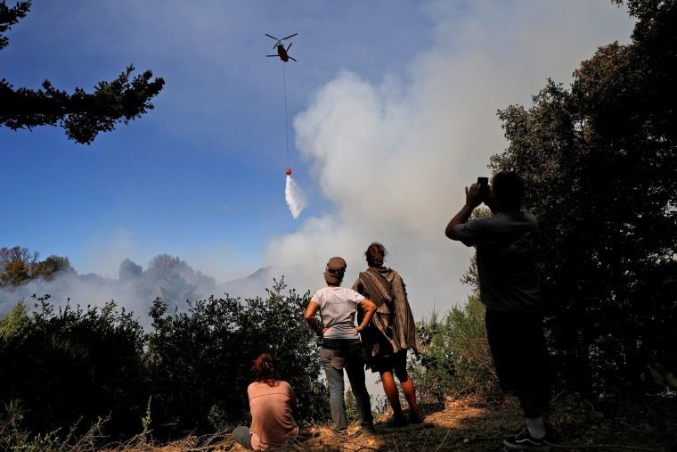 Image: A group of residents who remained despite the mandatory evacuation watch a firefighting helicopter make a drop near their properties along Summit road during the Loma Fire near Santa Cruz, California