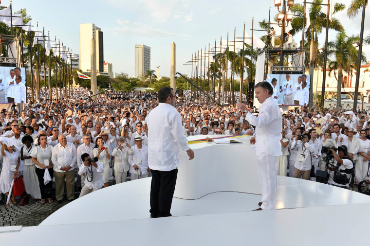 Image: Colombian President Santos and Marxist rebel leader Londono after signing an accord ending a half-century war that killed a quarter of a million people, in Cartagena