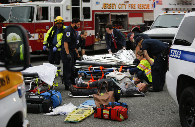 Image: People are treated for their injuries outside after a NJ Transit train crashed in to the platform