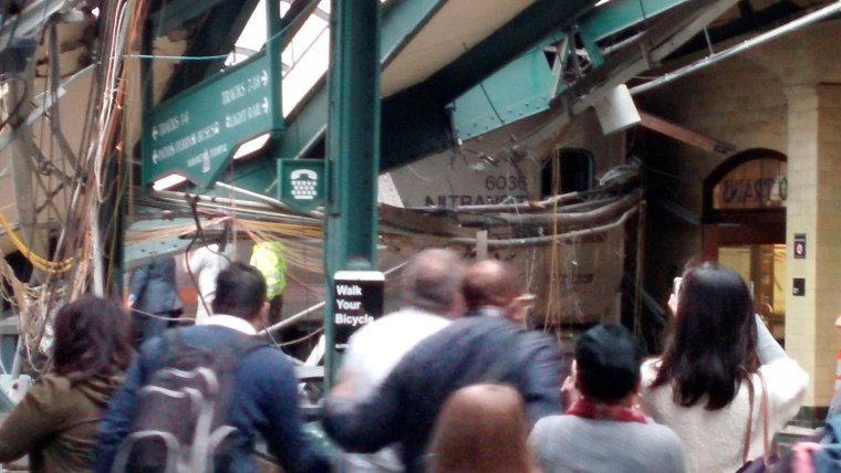 Image: Onlookers view a New Jersey Transit train that derailed and crashed through the station in Hoboken, New Jersey,
