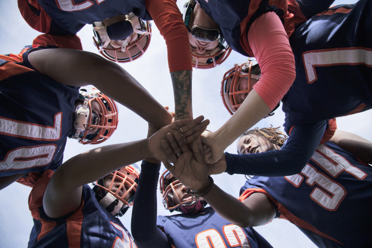 Female professional football players in huddle