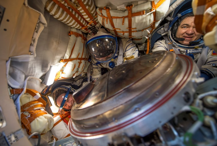 Image: The International Space Station (ISS) crew members are seen inside the Soyuz TMA-20M spacecraft capsule