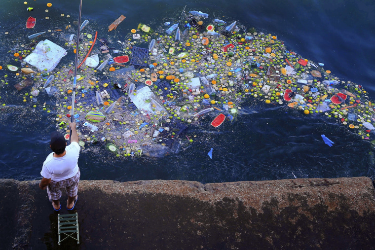 Image: A man holds a fishing rod as floating trash hits the coastline of the Mediterranean Sea in Beirut