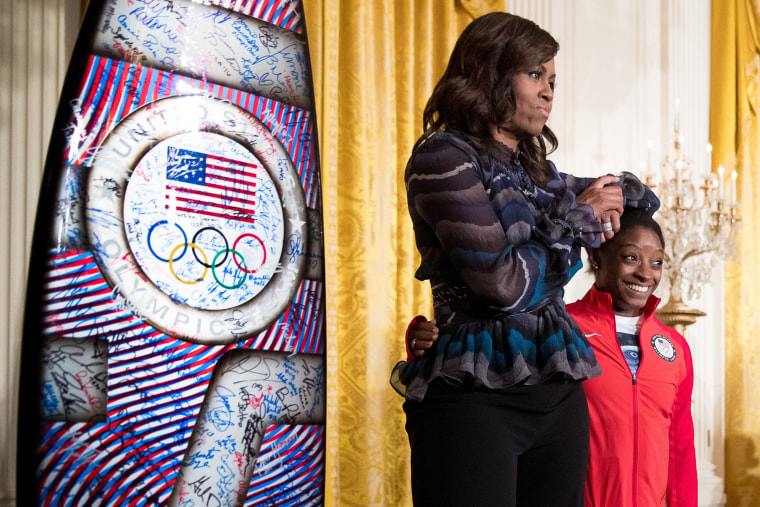 Image: Michelle Obama jokingly uses the head of US Olympics gymnast Simone Biles as an arm rest