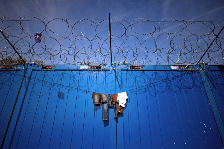 Image: Clothes hang on the barbed wires at a makeshift refugee and migrants camp
