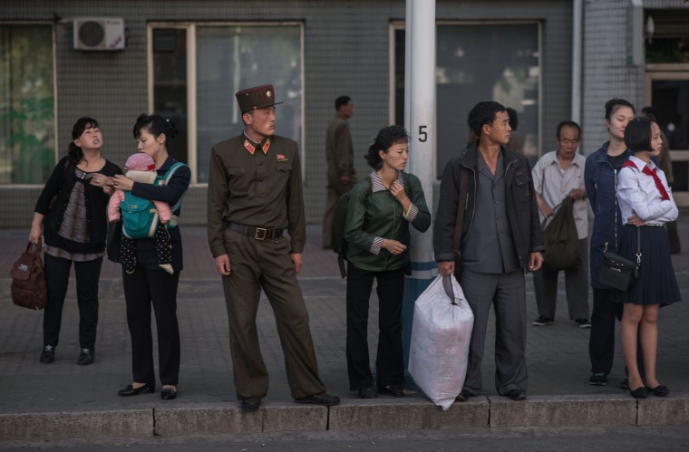 Image: Commuters wait for a bus during the morning rush hour in Pyongyang