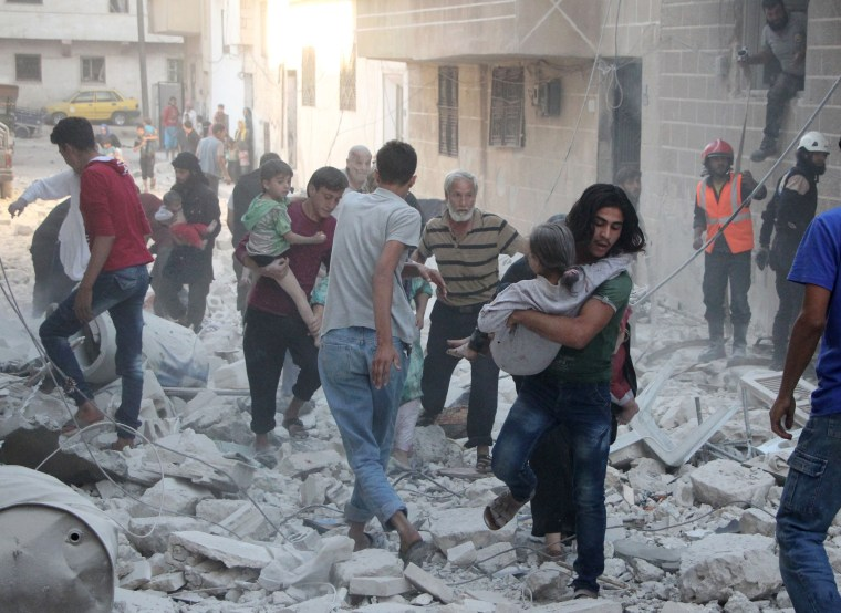 Image: Syrian men carry injured people amid the rubble of destroyed buildings in Idlib