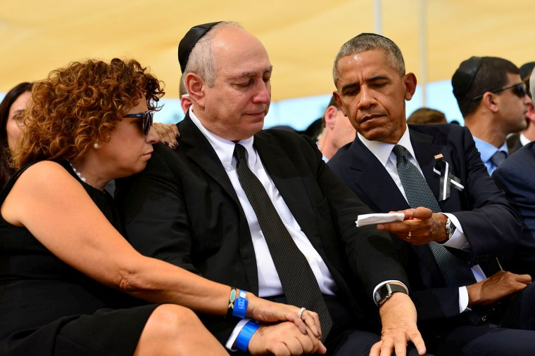 Image: U.S. President Barack Obama offers a tissue to Chemi Peres