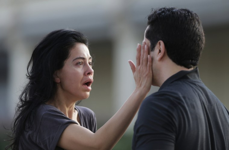 Image: Jennifer Molleda looks at the blood specked face of her husband after a shooting