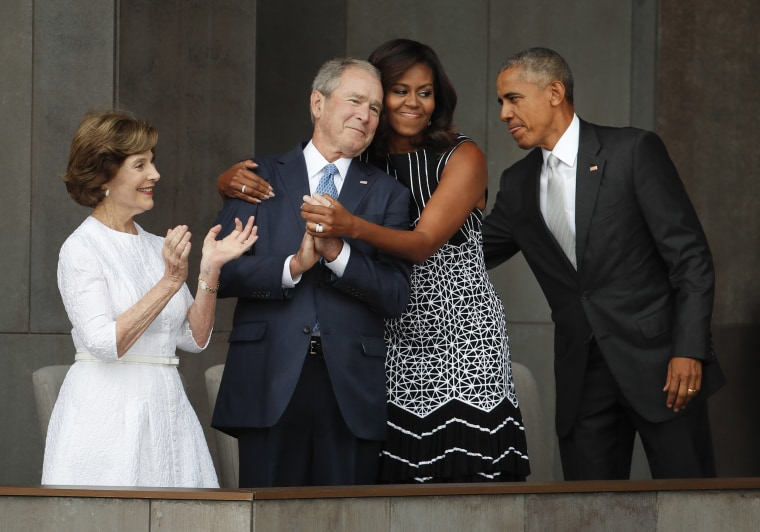 Image: First lady Michelle Obama hugs former President George W. Bush at the dedication ceremony of the Smithsonian Museum of African American History and Culture
