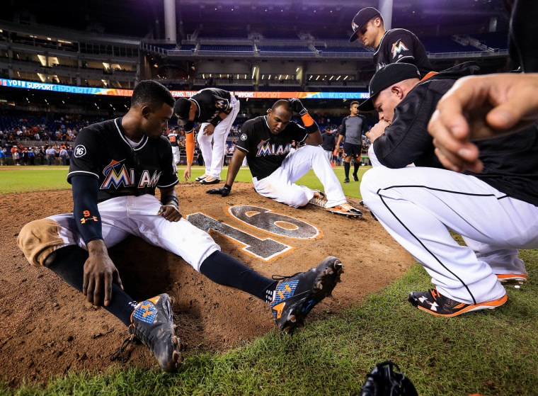 Image: Members of the Miami Marlins gather around the number of star pitcher Jose Fernandez on the pitching mound