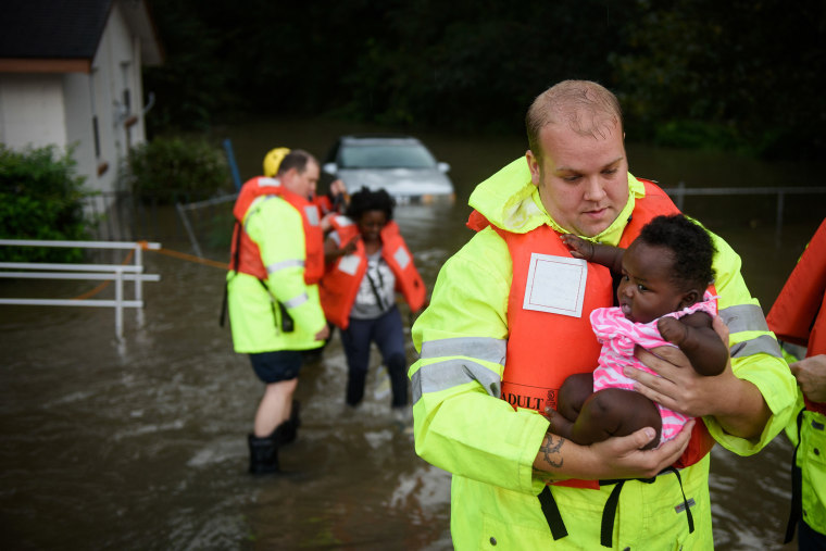 Image: A firefighter helps a family evacuate their flooded home in Fayetteville, N.C.
