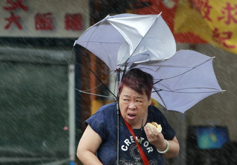 Image: A woman eats while struggling with her umbrella against powerful gusts of wind generated by typhoon Megi