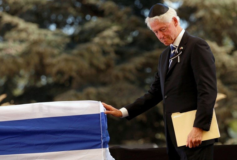 Image: Former US President Bill Clinton stands in front of the flag-draped coffin of the former Israeli President Shimon Peres