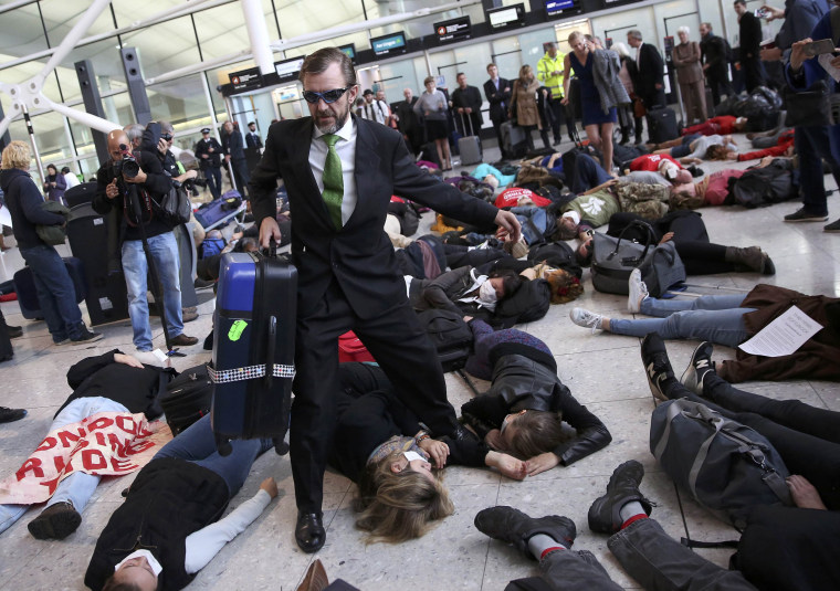 Image: Climate activist group Reclaim the Power lie on the ground and carry luggage during a protest against airport expansion plans at Heathrow Airport in London