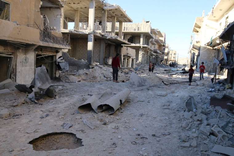 Image: People inspect a damaged site after airstrikes on the rebel held Sheikh Fares neighbourhood of Aleppo